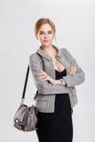 Porträt der jungen schönen Geschäftsfraublondine im schwarzen Kleid und mit Tasche auf grauem Hintergrund Lizenzfreies Stockbild