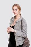 Porträt der jungen schönen Geschäftsfraublondine im schwarzen Kleid und mit Tasche auf grauem Hintergrund Lizenzfreie Stockfotos