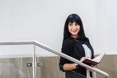 Porträt der jungen schönen glücklichen brunette Frau gekleidet in einem schwarzen Anzug, der mit einem Notizbuch, stehend im Büro stockbilder
