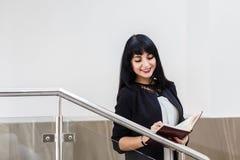 Porträt der jungen schönen glücklichen brunette Frau gekleidet in einem schwarzen Anzug, der mit einem Notizbuch, stehend im Büro lizenzfreies stockfoto