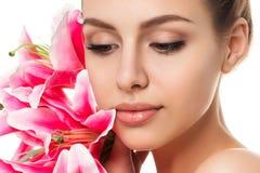 Porträt der jungen schönen kaukasischen Frau mit rosa Lilien Lizenzfreie Stockbilder