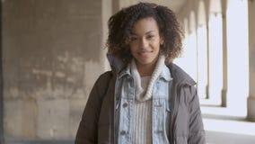 Porträt der jungen schönen Mischrassefrau mit dem Afrohaarschnittgehen stock footage