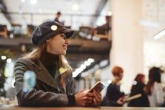 Porträt der jungen schönen modernen brunette Frau, die im Café sitzt stockfotografie