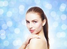 Porträt der jungen, schönen und gesunden Frau: über blauem undeutlichem Hintergrund Stockfoto