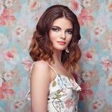 Porträt der jungen Schönheit auf einem Hintergrund von Blumen Stockfotos