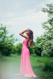 Porträt der jungen Schönheit aufwerfend unter blühenden Bäumen des Frühlinges Lizenzfreies Stockbild