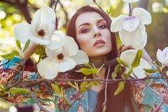 Porträt der jungen Schönheit aufwerfend unter blühenden Bäumen mit rosa Lidschatten Stockbilder