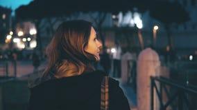 Porträt der jungen Schönheit Kamera betrachtend und herauf Haar tuend Mädchendrehungen, geht weg in die Abendstadt Stockfoto