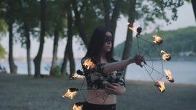 Porträt der jungen Schönheit in der Maske, die eine Show mit Flammenstellung auf Riverbank vor Bäumen durchführt talentiert stock footage