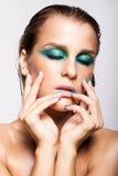 Porträt der jungen Schönheit mit grünem nassem glänzendem Make-up Stockbild