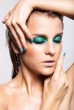 Porträt der jungen Schönheit mit grünem nassem glänzendem Make-up Stockbilder
