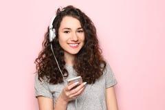 Porträt der jungen Schönheit mit Smartphone und Kopfhörern auf Farbhintergrund stockfotos