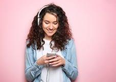Porträt der jungen Schönheit mit Smartphone und Kopfhörern auf Farbhintergrund lizenzfreie stockfotos