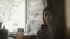 Porträt der jungen Schönheit sitzend im Café nahe dem Fenster und den Smartphone verwendend, das Internet surfend stock video