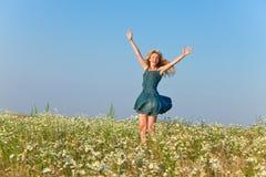 Porträt der jungen schlanken Frau in den Blue Jeans sundress auf dem Gebiet von camomiles an einem sonnigen Tag Lizenzfreies Stockbild