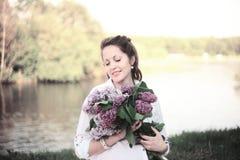 Porträt der jungen schwangeren Frau mit einem Blumenstrauß der Flieder auf einem Ba Lizenzfreies Stockbild
