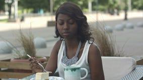 Porträt der jungen schwarzen Frau, die Café im im Freien isst stock footage