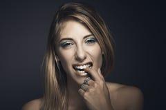 Porträt der jungen sexy Frau, die ihre Finger beißt Stockfoto