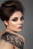 Porträt der jungen sinnlichen Brunettefrau mit schwarzem Flügel Lizenzfreies Stockfoto