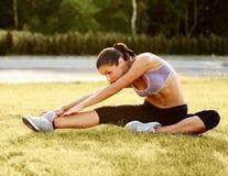 Porträt der jungen sportlichen Frau, die Übung ausdehnend tut. Athlet Lizenzfreies Stockbild