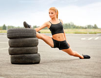 Porträt der jungen sportlichen Frau, die Übung ausdehnend tut. Athlet Stockbild