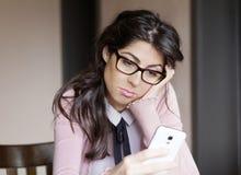 Porträt der jungen traurigen Frau, die schlechten sms empfangend Innen Lizenzfreie Stockbilder