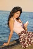 Porträt der jungen traurigen Frau, schlechte sms auf dem Strand empfangend Stockfoto
