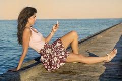 Porträt der jungen traurigen Frau, schlechte sms auf dem Strand empfangend Stockfotos