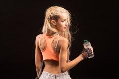 Porträt der jungen und gesunden Blondine mit Springseil und bott Lizenzfreie Stockbilder