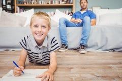 Porträt der Jungenzeichnung im Buch während Vater, der auf Sofa sitzt Lizenzfreie Stockfotografie