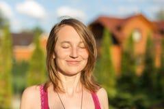 Porträt der kaukasischen Frau des jungen Brunette, die draußen mit geschlossenen Augen lächelt Goldenes Stundensonnenlicht bei So Stockfoto