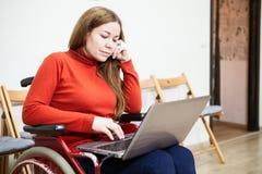 Porträt der kaukasischen Frau im ungültigen Rollstuhl, der mit Laptop auf Knien, Behinderter arbeitet Lizenzfreies Stockbild