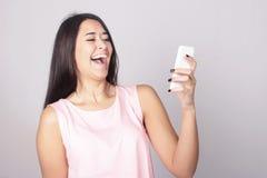 Porträt der kaukasischen jungen Frau, die einen Handy verwendet stockfoto