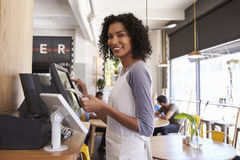 Porträt der Kellnerin At Cash Register in der Kaffeestube Lizenzfreies Stockfoto