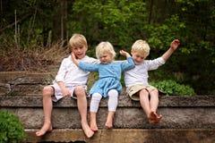 Porträt der kleinen Schwester Child Pushing ihre Brüder weg lizenzfreies stockfoto