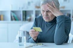 Porträt der kranken älteren Frau, die zu Hause Medizin nimmt lizenzfreie stockfotos