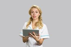 Porträt der Krankenschwester, die eine digitale Tablette verwendet Lizenzfreie Stockbilder