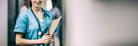 Porträt der Krankenschwester lächelnd während Holdingdatei lizenzfreie stockbilder