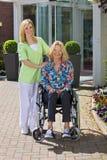 Porträt der Krankenschwester mit älterer Frau im Rollstuhl Lizenzfreie Stockbilder