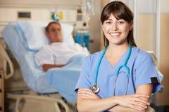 Porträt der Krankenschwester mit Patienten im Hintergrund Stockbild