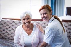 Porträt der lächelnden älteren Frau und der Ärztin im Wohnzimmer lizenzfreies stockbild
