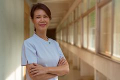 Porträt der lächelnden älteren Krankenschwesterstellung am Krankenhausbalkon stockfotografie