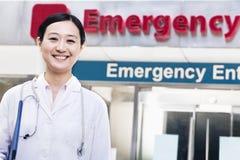 Porträt der lächelnden Ärztin außerhalb des Krankenhauses, Unfallstation unterzeichnen herein den Hintergrund Stockbild