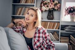 Porträt der lächelnden blonden Frau in einem Raum mit Lesebüchern O Lizenzfreies Stockfoto
