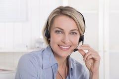 Porträt der lächelnden blonden reifen Frau, die mit Kopfhörer arbeitet. Stockfotos