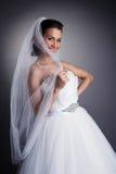 Porträt der lächelnden Braut versteckend hinter Schleier Stockbild