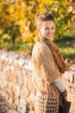 Porträt der lächelnden eleganten Brunettefrau im Herbstpark stockbilder