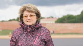 Porträt der lächelnden erwachsenen Frau alterte 60s draußen stock video