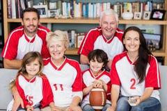 Porträt der lächelnden Familie mit den Großeltern, die amerikanisches Fußballspiel aufpassen stockbilder