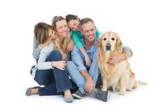 Porträt der lächelnden Familie sitzend zusammen mit ihrem Hund lizenzfreies stockfoto